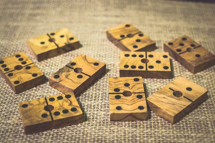 close up of nine wood domino tiles on brown table