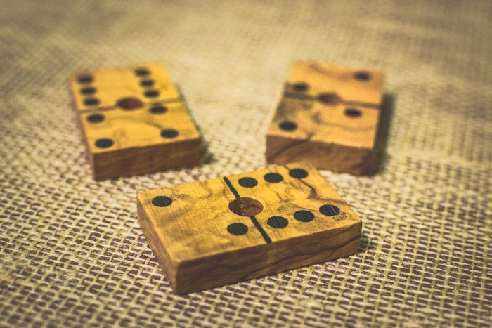 close up of three wooden domino tiles on a brown table using rule of odds composition
