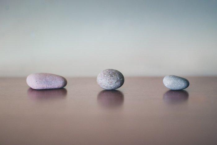 three grey stones on wood surface