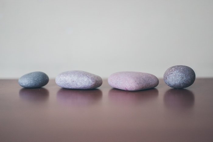 four grey stones lined up on a wooden surface