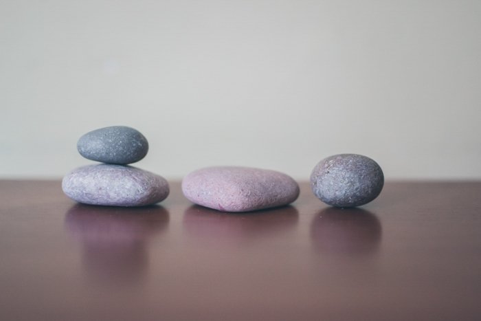 four grey stones on a wooden surface, two stacked, using rule of odds composition