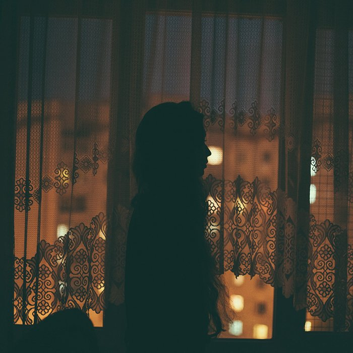 Atmospheric portrait of a female model posing against a window at night- creative selfie poses and ideas