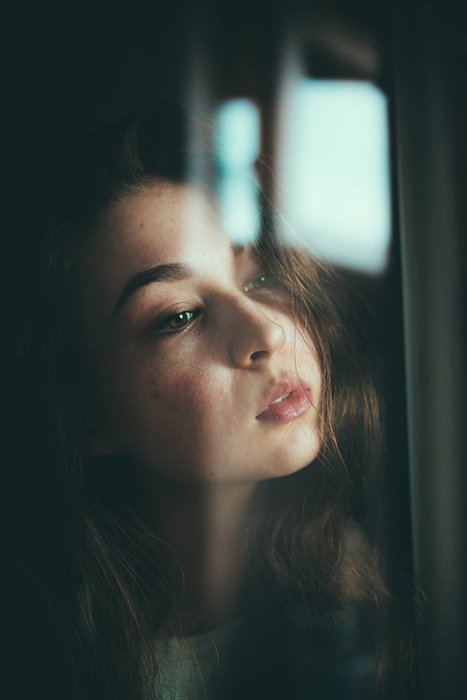 Atmospheric portrait of a female model looking through a window - great selfie poses