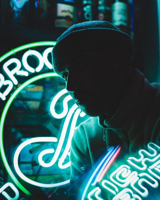 Low light portrait of a man posing in front of a neon sign at night