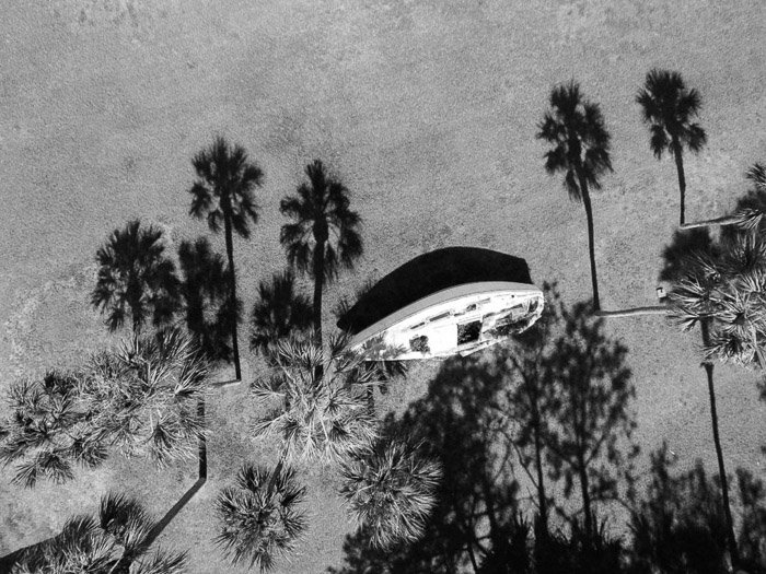Overhead black and white photo of a wooden boat on a beach surrounded by shadows of palm trees - shadow photography