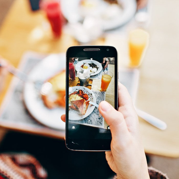 A person taking a food photography shot with a smartphone