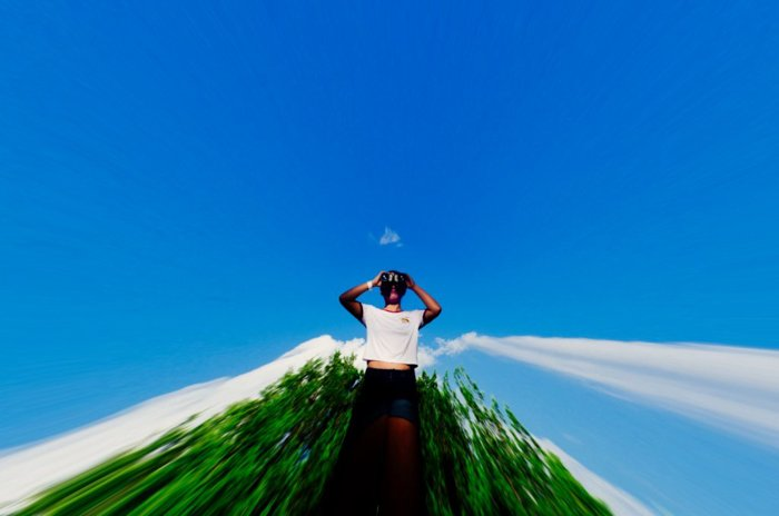 sbstract photo of a man in a white shirt posing in front of dark green trees and bright blue sky