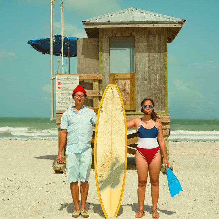 couple on the beach posing for a photo holding a surfboard between them - smartphone photography styles