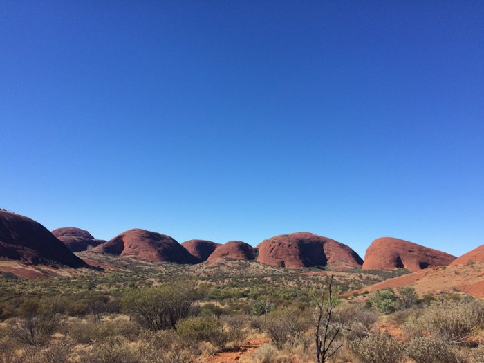 rounded hills in desert against a deep blue sky