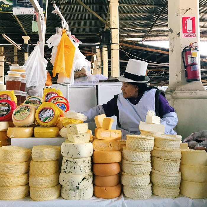 man at a market selling whole cheese rounds- smartphone photography styles