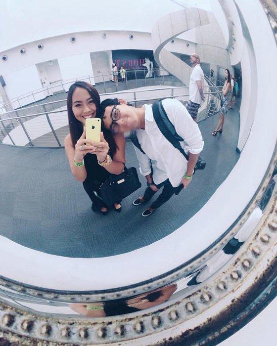 couple taking selfie through a circle mirror at a mall