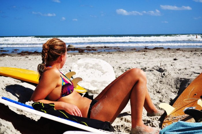 woman in a bikini lounging on the beach looking out at the blue sea