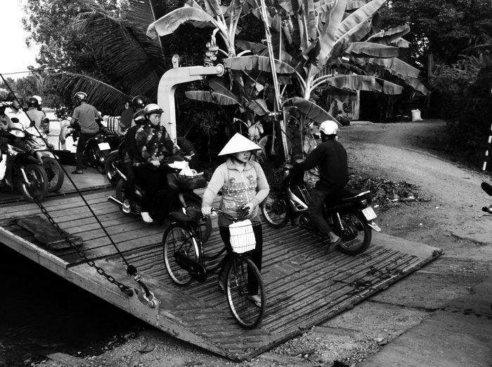 A black and white smartphotne street photo of people walking off a ferry with bicycles