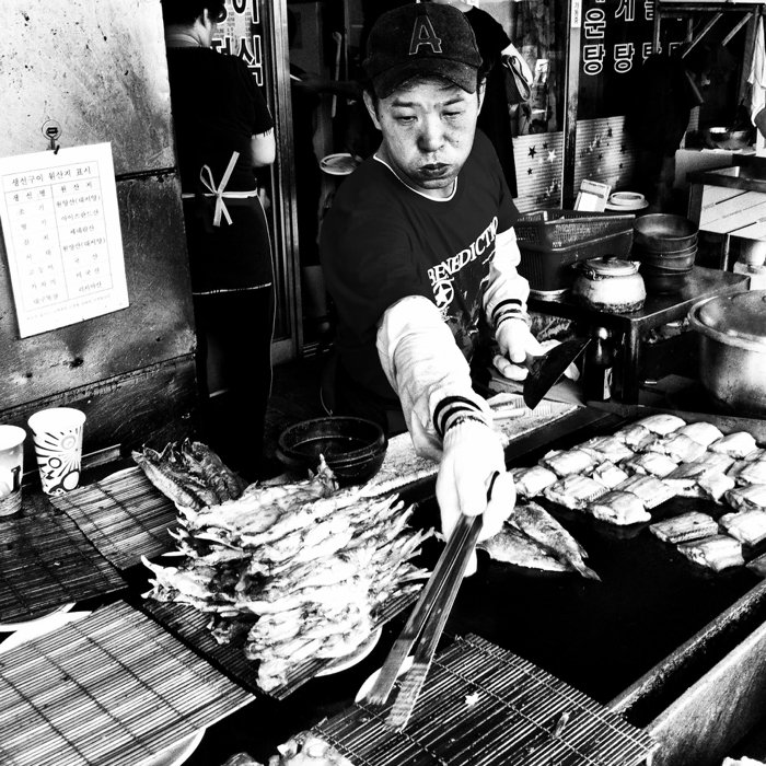 black and white smartphotne street photo of a market vendor frying fish