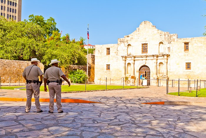 two men looking across a cobblestone street at The Alamo in Texas