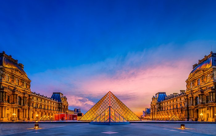 The Louvre in France, lit by golden yellow lights, glowing against the deep blue sky at dusk - travel photography destinations