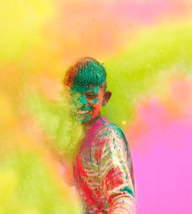 a boy covered in colourful paint, standing in a cloud of colours at a festival