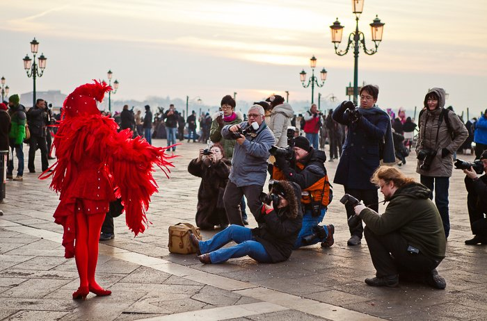 people taking photos of a street performer in a feathery red outfit