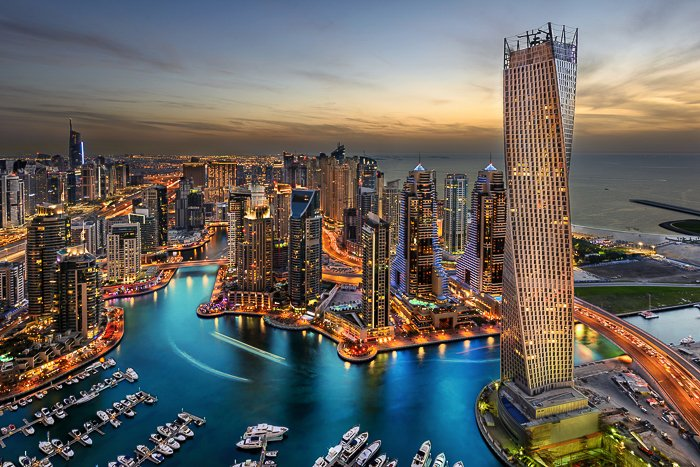 UAE cityscape at dusk, lit by golden lights, deep blue waters of the creek