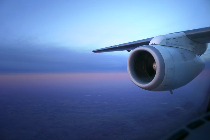 View from an airplane window of the airplane wing and engine, against a blue, purple, and orange dusk