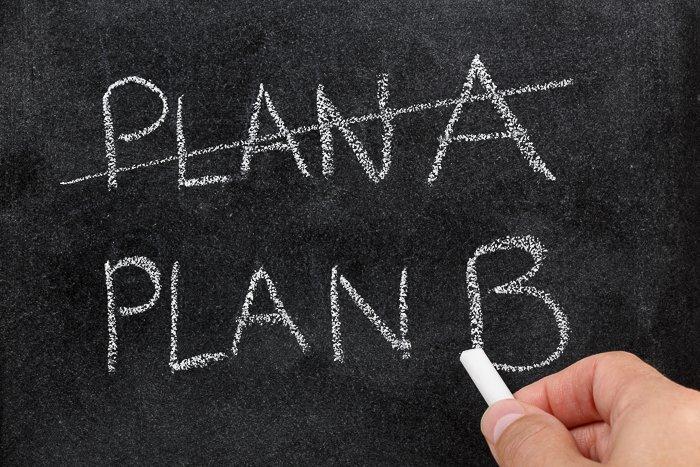 Hand holding a piece of chalk, writing on a blackboard, Plan A, Plan B