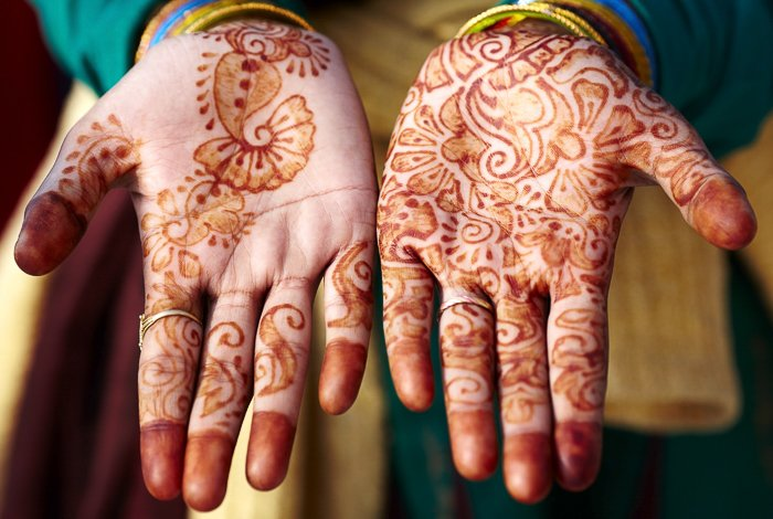 close up of hands, palms up, with henna design on them