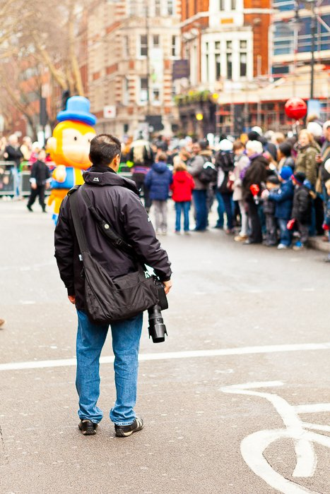 man in a black parka holding a DSLR watching people in a parade at a distance