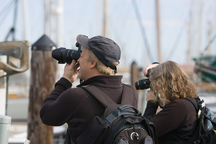 Man and woman at a pier with DSLRs taking photos