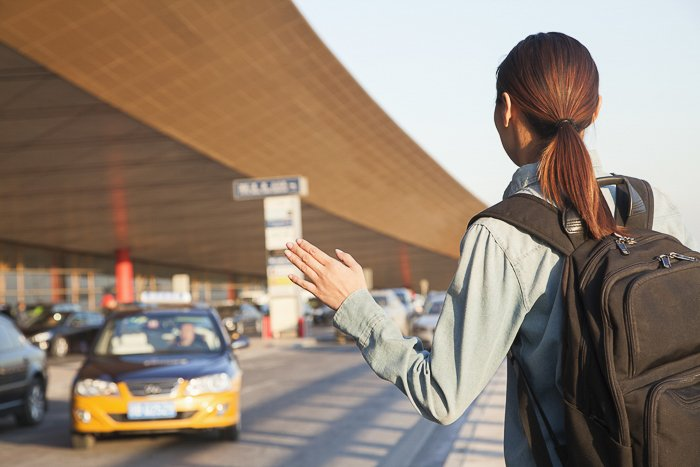 brunette woman with a backpack hailing down a taxi cab at the airport