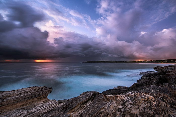 calm waters at a rocky shore, against a purple blue sky, the sunset fading on the horizon. Shutter speed at 30 sec - water photography settings