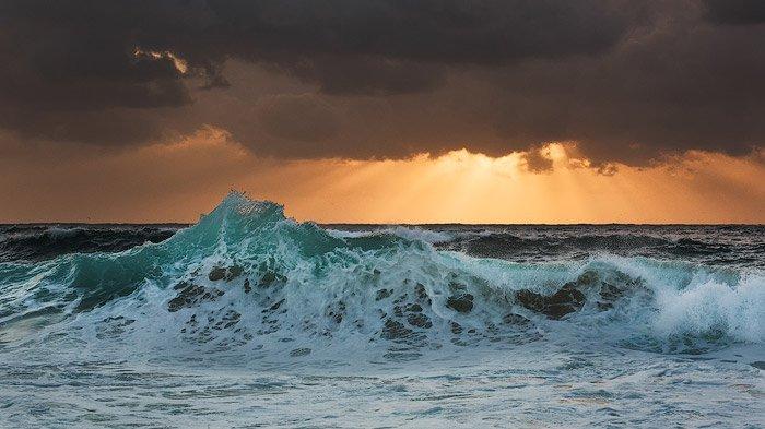 foamy waves crashing onto the shore, golden sun beams peeking from the dark clouds on the horizon. Shutter speed is 1/50 sec