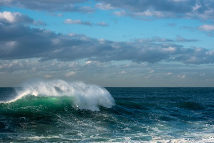 waves in turquoise blue green crystal waters, a cloudy sky overhead - water photography settings