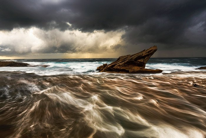 rock platform outcrop in the choppy sea waters, dark cloudy skies, a fading golden sunset on the horizon - water photography settings