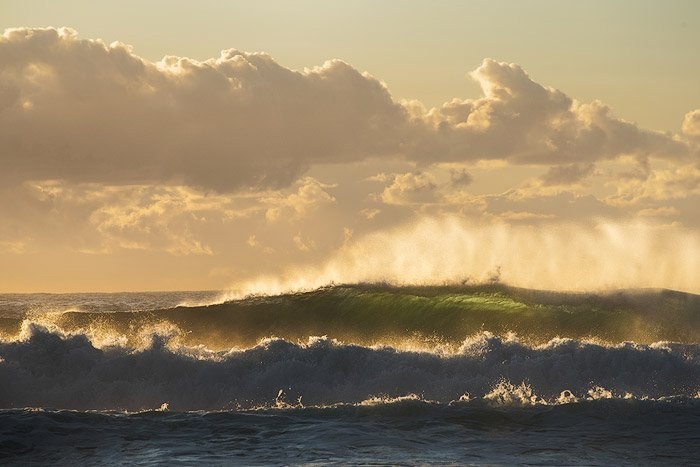 Sunrise seascape with unrest sea and green water and beautiful incoming backlit waves - water photography settings