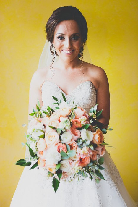 smiling brunette bride holding a large bouquet with a yellow wall behind her - wedding photo editing trends