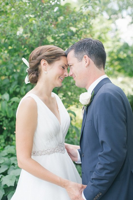 bright and airy photo of newly weds standing outdoors, their foreheads touching, with the trees behind them