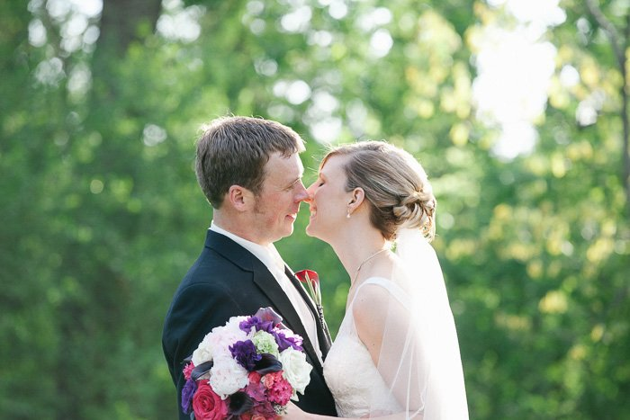 A smiling bride and groom outdoors against a backdrop of green leaves about to kiss - best wedding photo editing tips