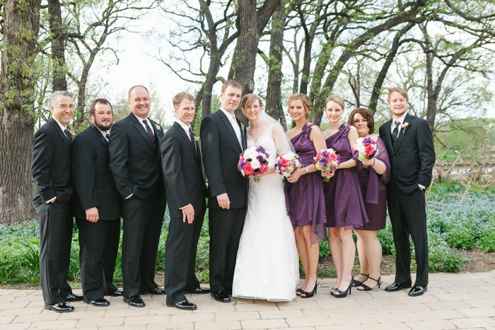 A wedding entourage with groomsmen and bridesmaids in purple outdoors against sparse spring trees