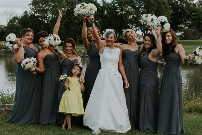 darker photo of bride with flower girl in a yellow dress, and bridesmaids in grey gowns standing in front of a lake, smiling and holding bouquets up