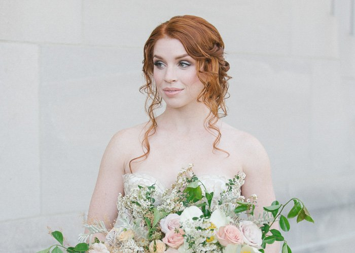headshot of a redhead bride against a plain white background, holding a large bouquet of flowers - best wedding photo editing tips