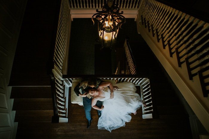 view from atop the stairs of a bride lying down on her groom's lap, on a recliner, the room dimply lit by a vintage chandelier