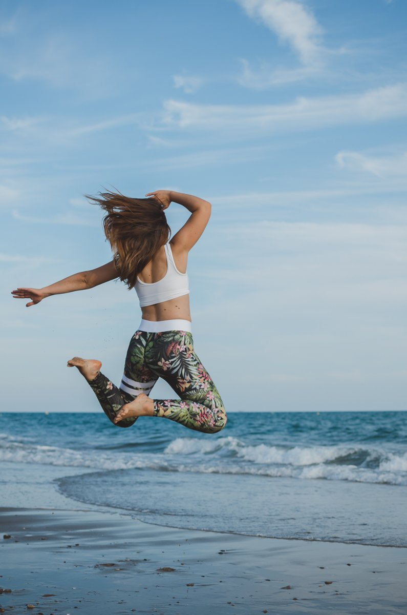 A girl in sports clothes jumping energetically on the beach shot using af mode
