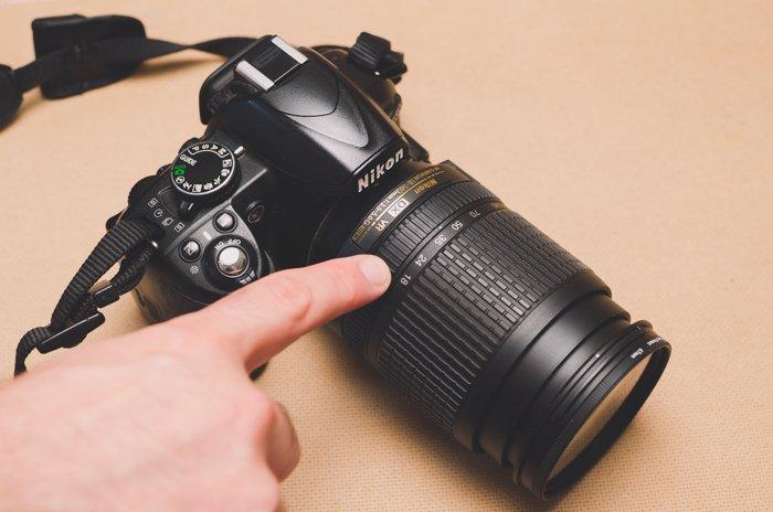 A person pointing to autofocus mode on a Nikon DSLR