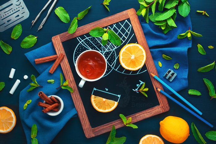 A blue and orange themed flat lay including oranges and teacups on a chalkboard