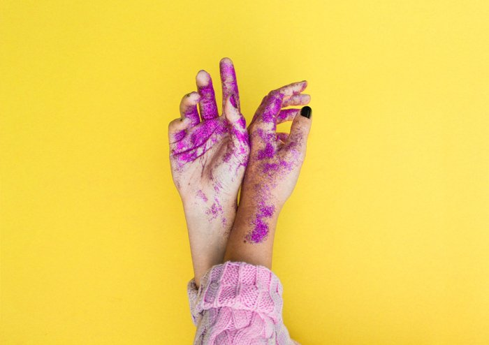 A fun image of paint and glitter covered hands featuring strong use of complementary colors yellow and purple