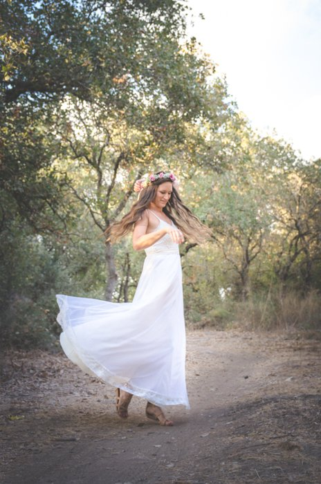 A girl in wedding dress dancing in a forest - learn photography camera settings