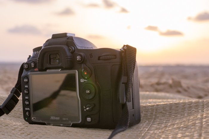 A DSLR photography camera resting on cloth at the beach