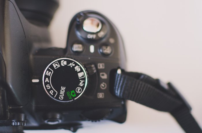 The camera settings button on a DSLR camera, set to aperture priority mode