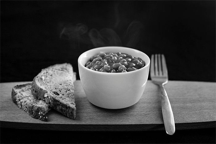 A black and white food photography shot of baked beans and bread on a wooden tray