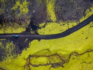 Aerial shot of a blue car on a road